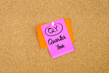 quarter note: Business Acronym QY Quarter Year written on paper note pinned on cork board with white thumbtack, copy space available