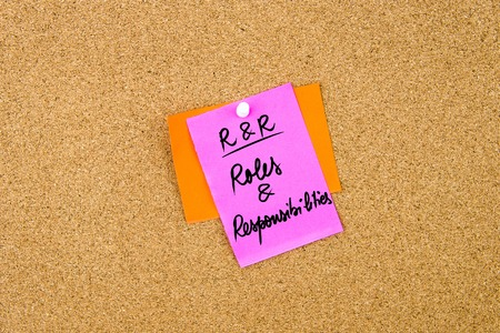 responsibilities: Business Acronym RR Roles and Responsibilities written on paper note pinned on cork board with white thumbtack, copy space available Stock Photo