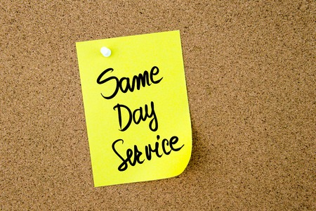 Same Day Service written on yellow paper note pinned on cork board with white thumbtack, copy space available Stock Photo