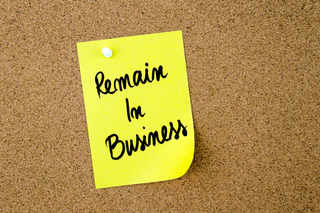 remain: Remain In Business written on yellow paper note pinned on cork board with white thumbtack, copy space available
