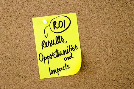 impacts: Business Acronym ROI Results, Opportunities and Impacts written on yellow paper note pinned on cork board with white thumbtack, copy space available