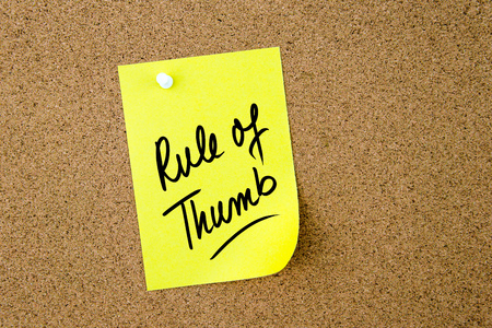 Rule Of Thumb written on yellow paper note pinned on cork board with white thumbtack, copy space available