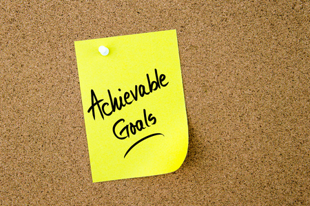achievable: Achievable Goals written on yellow paper note pinned on cork board with white thumbtack, copy space available