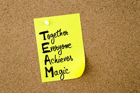 achieves: Business Acronym TEAM as Together Everyone Achieves Magic written on yellow paper note pinned on cork board with white thumbtack, copy space available