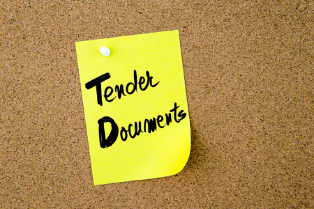 td: Business Acronym TD Tender Documents written on yellow paper note pinned on cork board with white thumbtack, copy space available
