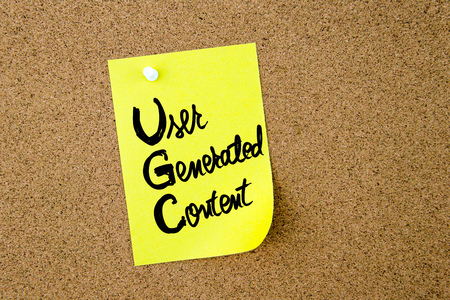 Business Acronym UGC User Generated Content written on yellow paper note pinned on cork board with white thumbtack, copy space available