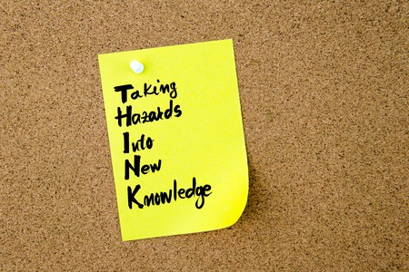 hazards: Business Acronym THINK Taking Hazards Into New Knowledge written on yellow paper note pinned on cork board with white thumbtack, copy space available Stock Photo