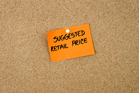 suggested: SUGGESTED RETAIL PRICE written on orange paper note pinned on cork board with white thumbtacks, copy space available Stock Photo
