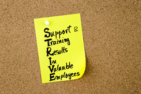 strive: Business Acronym STRIVE as Support and Training Results In Valuable Employees written on yellow paper note pinned on cork board with white thumbtack, copy space available
