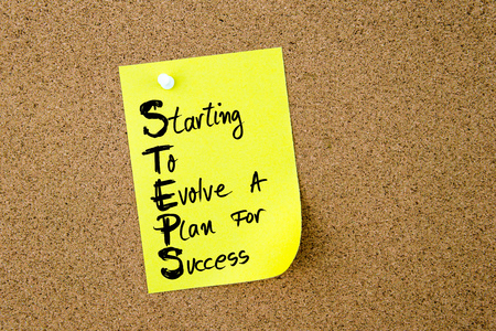 evolve: Business Acronym STEPS Starting To Evolve A Plan For Success written on yellow paper note pinned on cork board with white thumbtack, copy space available Stock Photo