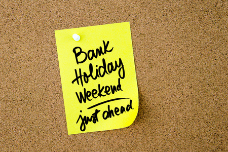 Bank Holiday Weekend Just Ahead written on yellow paper note pinned on cork board with white thumbtack, copy space available