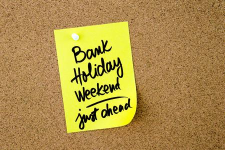 银行假日周末前面撰写在黄色纸笔记上钉在软木板有白色图钉的黄色纸张,副本空间可用