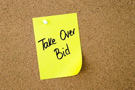 bid: Take Over Bid written on yellow paper note pinned on cork board with white thumbtack, copy space available