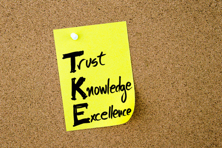 Business Acronym TKE Trust Knowledge Excellence written on yellow paper note pinned on cork board with white thumbtack, copy space available