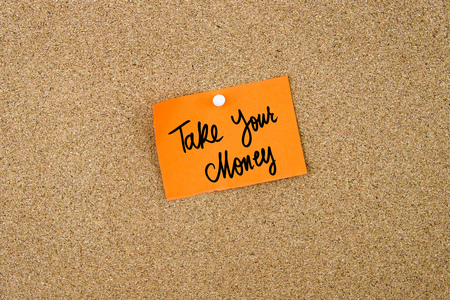 take a note: Take Your Money written on orange paper note pinned on cork board with white thumbtacks, copy space available