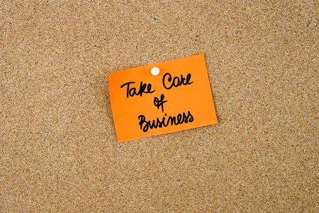 take a note: TAKE CARE OF BUSINESS written on orange paper note pinned on cork board with white thumbtacks, copy space available