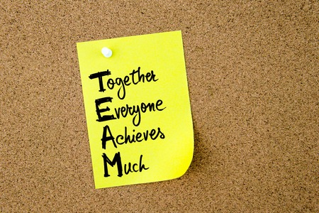 achieves: Business Acronym TEAM as Together Everyone Achieves Much written on yellow paper note pinned on cork board with white thumbtack, copy space available