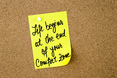 begins: Life Begins At The End Of Your Comfort Zone written on yellow paper note pinned on cork board with white thumbtack, copy space available