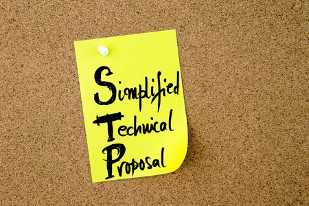 simplified: Business Acronym STP Simplified Technical Proposal written on yellow paper note pinned on cork board with white thumbtack, copy space available