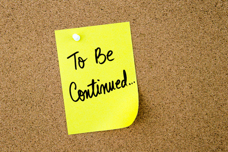 continued: To Be Continued written on yellow paper note pinned on cork board with white thumbtack, copy space available
