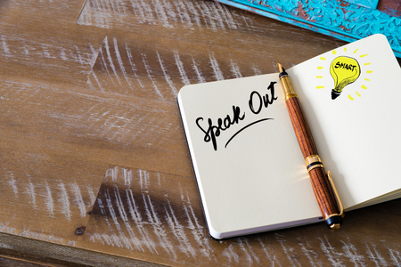 speak out: Handwritten text Speak Out with fountain pen on notebook. Concept image with copy space available.