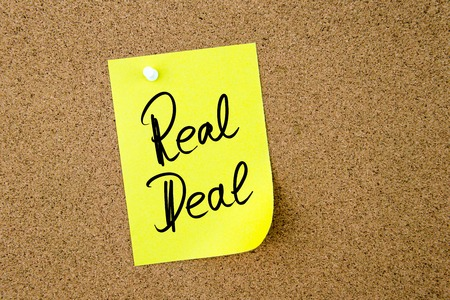 rd: Business Acronym RD Real Deal written on yellow paper note pinned on cork board with white thumbtack, copy space available