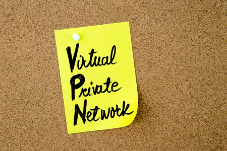 vpn: Business Acronym VPN Virtual Private Network written on yellow paper note pinned on cork board with white thumbtack, copy space available