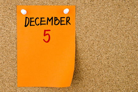 '5 december': 5 DECEMBER written on orange paper note pinned on cork board with white thumbtacks, copy space available