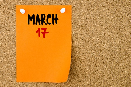17 march: 17 MARCH written on orange paper note pinned on cork board with white thumbtacks, copy space available