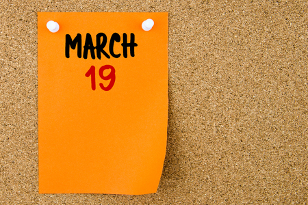 19: 19 MARCH written on orange paper note pinned on cork board with white thumbtacks, copy space available