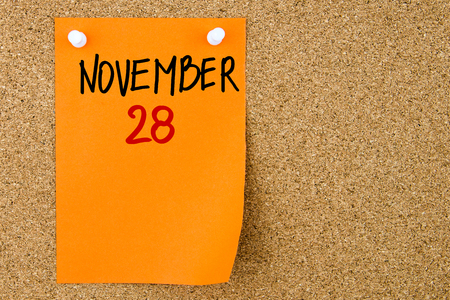 28: 28 NOVEMBER written on orange paper note pinned on cork board with white thumbtacks, copy space available Stock Photo