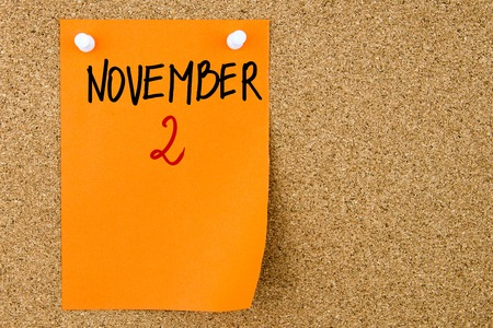 2 november: 2 NOVEMBER written on orange paper note pinned on cork board with white thumbtacks, copy space available Stock Photo