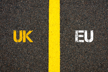 yes or no to euro: Antonym concept of UK United Kingdom versus EU EUROPEAN UNION written over tarmac, road marking yellow paint separating line between words