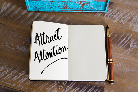 attract: Text Attract Attention handwritten on notebook