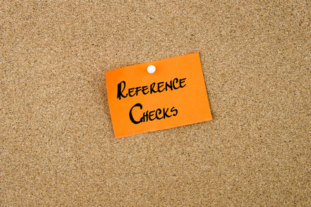 thumbtack: Reference Checks written on orange paper note note pinned on cork board with white thumbtack, copy space available
