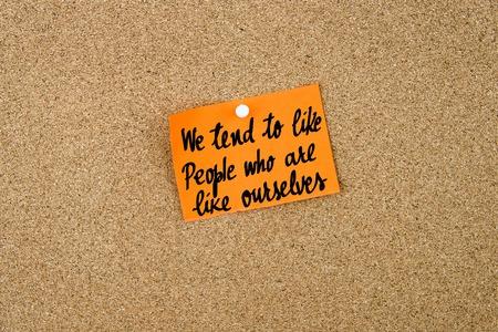 Nos tienden a como las personas que son como nosotros por escrito sobre la nota de color naranja nota de papel depositado en el tablón de corcho con chincheta blanco, copia espacio disponible