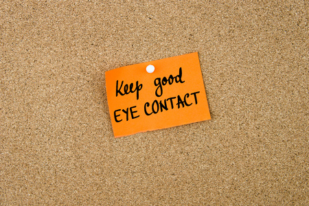thumbtack: Keep Good Eye Contact written on orange paper note note pinned on cork board with white thumbtack, copy space available