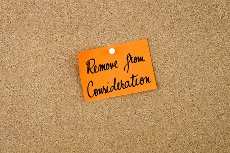thumbtack: Remove From Consideration written on orange paper note note pinned on cork board with white thumbtack, copy space available