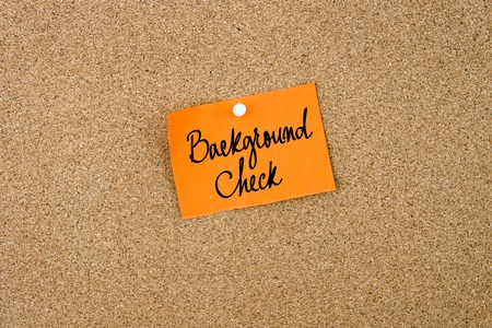 thumbtack: Background Check written on orange paper note note pinned on cork board with white thumbtack, copy space available Stock Photo