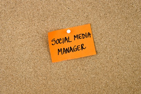 thumbtack: Social Media Manager written on orange paper note note pinned on cork board with white thumbtack, copy space available