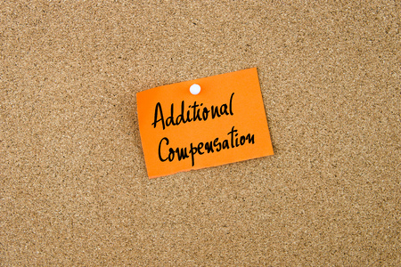 additional compensation: Additional Compensation written on orange paper note note pinned on cork board with white thumbtack, copy space available