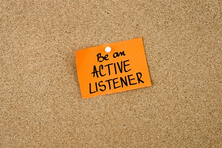 listener: Be An Active Listener written on orange paper note note pinned on cork board with white thumbtack, copy space available