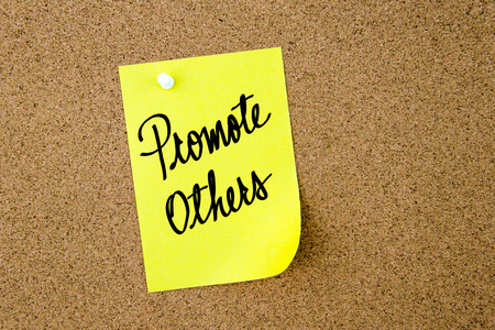 others: Promote Others written on yellow paper note pinned on cork board with white thumbtacks, copy space available