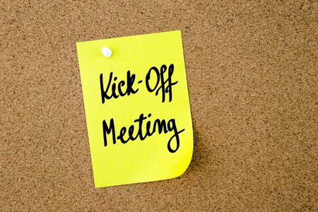 kickoff: Kick-Off Meeting written on yellow paper note pinned on cork board with white thumbtacks, copy space available
