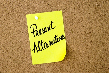 yellow thumbtacks: Present Alternatives written on yellow paper note pinned on cork board with white thumbtacks, copy space available Stock Photo