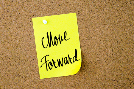 to move forward: Move Forward written on yellow paper note pinned on cork board with white thumbtacks, copy space available