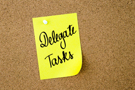 delegate: Delegate Tasks written on yellow paper note pinned on cork board with white thumbtacks, copy space available Stock Photo