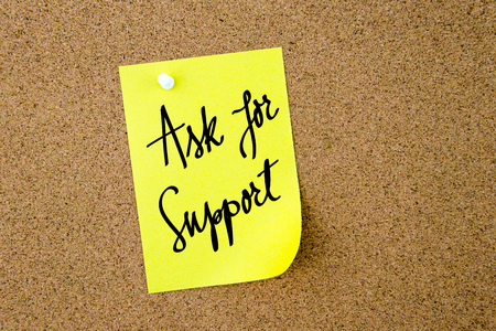 yellow thumbtacks: Ask For Support written on yellow paper note pinned on cork board with white thumbtacks, copy space available Stock Photo