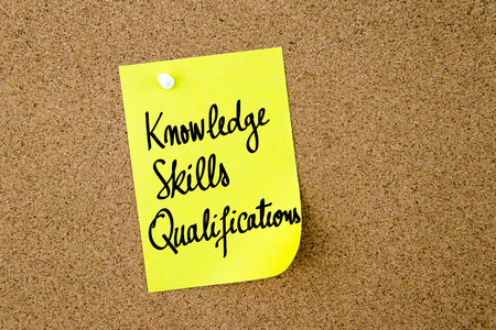qualifications: Knowledge Skills Qualifications written on yellow paper note pinned on cork board with white thumbtacks, copy space available