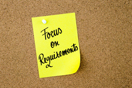 requirements: Focus On Requirements written on yellow paper note pinned on cork board with white thumbtacks, copy space available